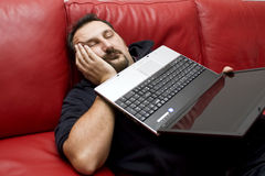 Sleeping man holding laptop. A view of a sleeping man slouched in a red leather sofa, holding a modern laptop computer Royalty Free Stock Photo
