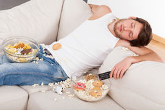 Sleeping man and junk food. A man sleeping on a couch in a mess of junk food Royalty Free Stock Images