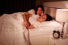 Sleeping man lying on bed with woman concerned comforting him at. Sleeping men lying on bed with women concerned comforting him at the night Stock Images