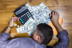 Sleeping man near the money with calculator. Young man in shirt tired and fell asleep counting money on a calculator with a pen in hand on a hundred dollar bill Royalty Free Stock Photography