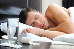 Sleeping. Man sleeping - pills on bed table. Headache Stock Photos