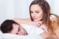 Sleeping man and pretty woman. Sleeping men and pretty awake women in bed Stock Images