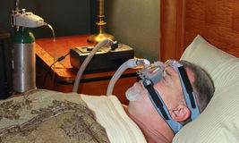 Sleeping Man (Profile) with CPAP and Oxygen. A man sleeping on his back is wearing a CPAP (continuous positive airway pressure) mask and supplemental Oxygen Royalty Free Stock Image