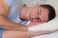 Sleeping man: Young handsome man sleeping comfortably  in bed Royalty Free Stock Images