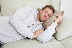 Sleeping man. Young handsome man sleeping at sofa in cozy apartment Stock Image