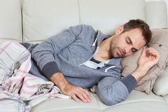 Sleeping man. Young handsome man sleeping at sofa in cozy apartment Royalty Free Stock Photography