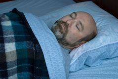 Sleeping Mature Man. Mature man sleeping on back; subdued lighting with blue night cast Stock Photography