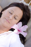 Sleeping mature woman with flower Royalty Free Stock Image