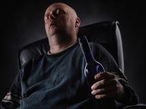 Sleeping middle aged alcoholic and wine bottle Stock Image