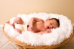 Sleeping Newborn. Newborn baby in diaper asleep in a wicker basket lined with a fluffy white blanket Royalty Free Stock Photo