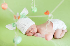 Sleeping newborn baby as Easter bunny with eggs Royalty Free Stock Images