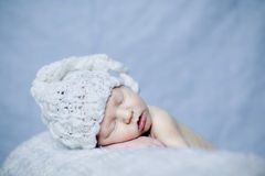 Sleeping newborn baby boy. In a white hat on a blue background Royalty Free Stock Image