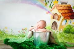 Sleeping newborn baby. Newborn baby boy sleeping in a silver metal bucket. Cartoon fairy house on background Stock Photo
