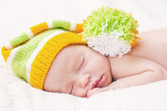 Sleeping newborn baby with bright hat Stock Photos