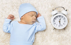 Sleeping Newborn Baby and Clock, New Born Sleep in Bed. Sleeping Newborn Baby and Clock, New Born Sleep in Blue Bodysuit in White Bed royalty free stock photography