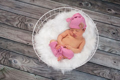 Sleeping Newborn Baby Girl Wearing Pink Sleeping Cap. Newborn baby girl sleeping in a white, wire basket lined with white faux fur. She is wearing a pink and Stock Photo