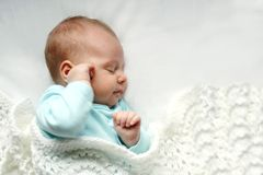 Sleeping Newborn Baby Girl in WHite Blankets. A sweet newborn infant girl is sleeping peacefully while snuggled in warm white blankets Stock Image