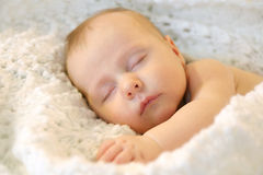 Sleeping Newborn Baby Girl in WHite Blankets. A sweet newborn infant girl is sleeping peacefully while snuggled in warm white blankets Royalty Free Stock Image