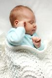 Sleeping Newborn Baby Girl in WHite Blankets. A sweet newborn infant girl is sleeping peacefully while snuggled in warm white blankets Stock Images