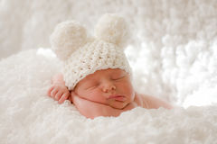 Sleeping newborn baby in knitted cap. A newborn baby sleeps on a white blanket with his little face resting on his arms. He is only 11 days old. Baby is wearing royalty free stock images