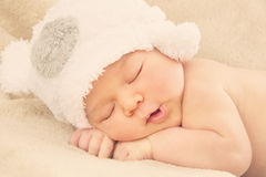 Sleeping newborn baby. Portrait of  newborn baby boy wearing funny bear shape hat sleeping on soft beige cover Stock Image
