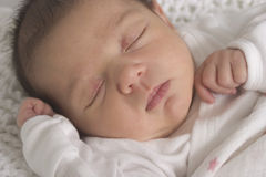 Sleeping newborn baby. Portrait of a sleeping two week old baby dressed in white Royalty Free Stock Images