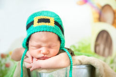 Sleeping newborn baby in a St. Patrick`s Day hat. Newborn baby boy wearing a St. Patrick`s Day hat sleeping in a silver metal bucket. Cartoon fairy house on Royalty Free Stock Images