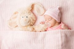 Sleeping Newborn Baby with Toy, New Born Kid Sleep covered by Blanket, Child Portrait. Two weeks old on pink background royalty free stock photo