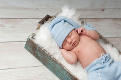 Sleeping Newborn Baby Wearing Pajamas. Newborn baby sleeping in a wooden crate and wearing light blue, upcycled pajamas with matching sleeping cap Royalty Free Stock Photos