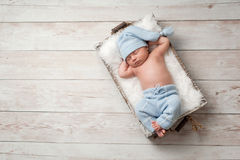 Sleeping Newborn Baby Wearing Pajamas. Newborn baby sleeping in a wooden crate on a whitewashed wooden floor. He is wearing light blue, upcycled pajamas with a Stock Image