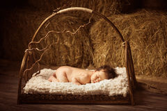 Sleeping newborn baby in a wooden lullaby bed. Stock Photography