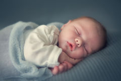 Sleeping newborn baby. In a wrap