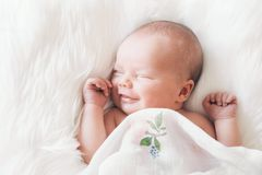Sleeping smiling newborn baby in a wrap on white blanket. Sleeping newborn baby in a wrap on white blanket. Beautiful portrait of little child girl 7 days, one Stock Image