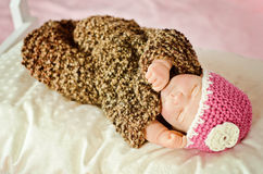 Sleeping Newborn Girl doll. Sleeping Newborn Baby Girl doll in white and pink flower hat wrapped up in a beautiful brown cocoon Royalty Free Stock Photo