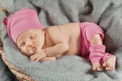 Sleeping newborn girl with a pink bow. Portrait of a newborn girl Royalty Free Stock Photo