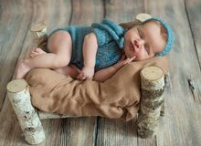 A sleeping newborn girl, in a wooden bed made of birch. Smiling in a blue knitted suit and hat. stock images