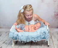 Sleeping newborn on little bed and his sister Stock Photo