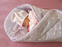 Sleeping newborn. One week old newborn girl sleeping in the Swaddle Wrap Blanket royalty free stock photos