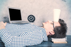 Sleeping on office desk. Young caucasian guy with blank laptop screen sleeping on office desktop with coffee cup on forehead. Mock up Stock Images