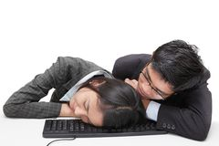 Sleeping office workers. Two bored or overworked office workers (Asian, male and female) sleeping together on a keyboard sitting at their desk. Isolated over Stock Image