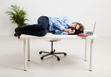 Sleeping in the office. Young man in the office and sleeping over is desk Royalty Free Stock Photography