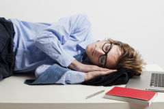 Sleeping in the office. Young man in the office and sleeping over is desk Stock Photography