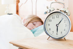 Sleeping. An old fashioned alarm clock with a young girl sleeping in the background stock photo