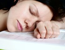 Sleeping over book. Young woman sleeping on her book stock images