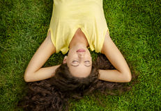 Sleeping over the grass. Portrait of a beautiful and happy young woman lying on the grass Royalty Free Stock Photo