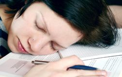 Sleeping over work. Young woman sleeping on her desk, over her work, with pen ,book and note stock photography