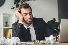 Sleeping overworked businessman with crumpled papers. On desk stock image