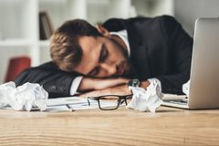 Sleeping overworked businessman with crumpled papers and eyeglasses. On desk stock photo