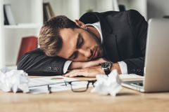 Sleeping overworked businessman with crumpled papers and laptop. On desk royalty free stock images