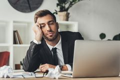 Sleeping overworked businessman with crumpled papers. At workplace royalty free stock photography